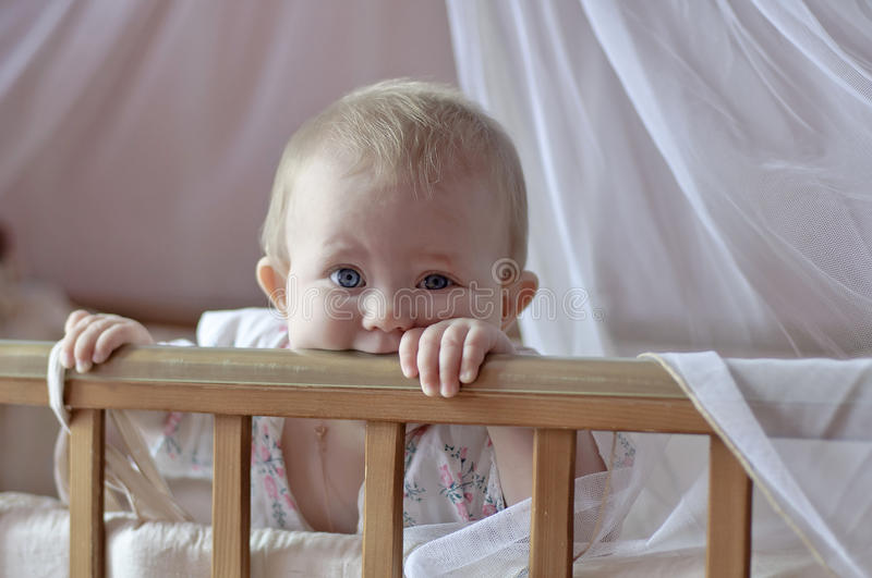 Baby in the cradle. Kid watching from the cradle royalty free stock photography