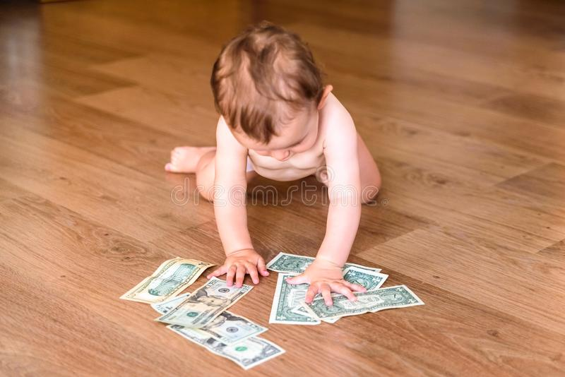Baby crawling on the floor in search of money, and finds dollar bills lying on the floor stock image
