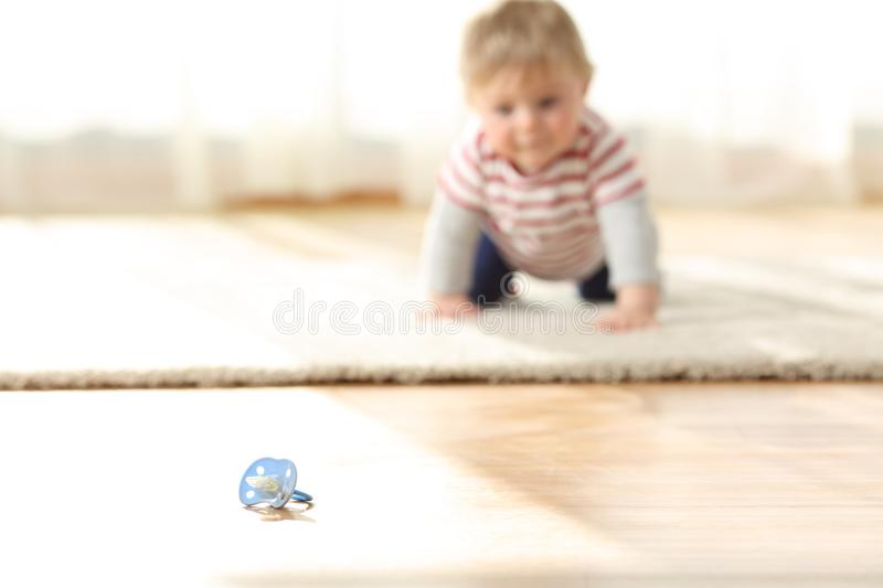 Baby crawling towards a dirty pacifier on the floor stock photos
