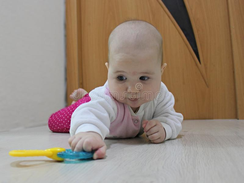 Baby crawling after a toy stock image