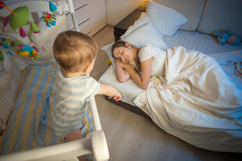 Baby in crib crying and trying to wake up mother that fell asleep stock images