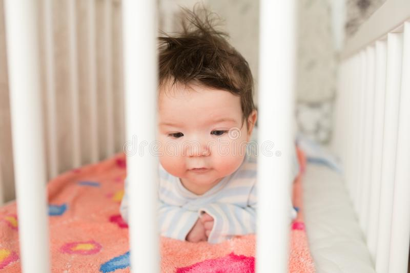 Baby in the crib. Funny baby in a white canopy bed. Children`s room interior and bedding for children. Laughing little boy playin. G in the basket of Moses royalty free stock photo