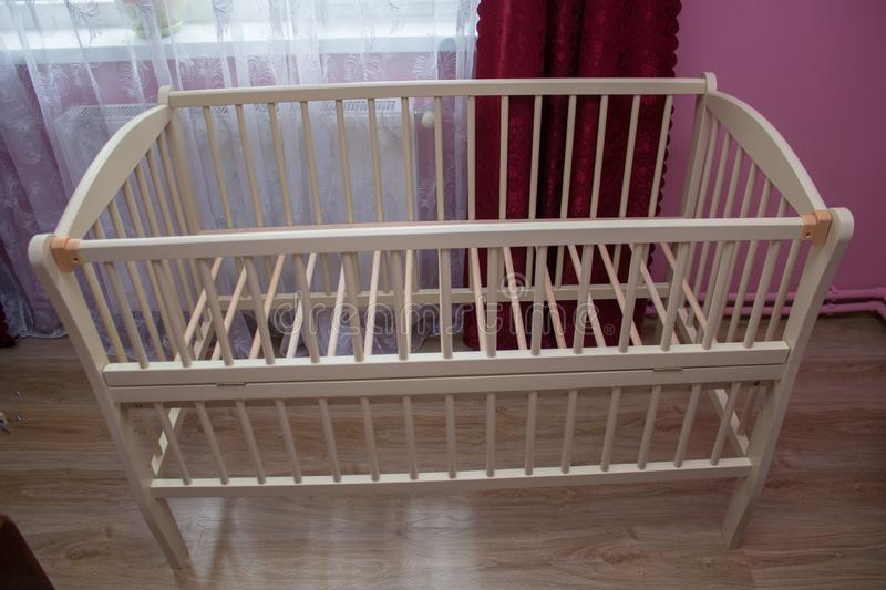 Baby crib without mattress,In the bedroom the parents prepared a baby crib for the baby. In the bedroom the parents prepared a baby crib for the baby royalty free stock photo
