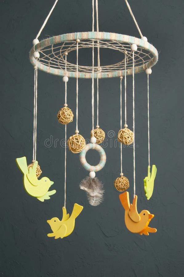 Baby crib mobile on gray background. Handmade multicolor baby crib mobile with wooden birdies and rattan balls on gray background stock photography