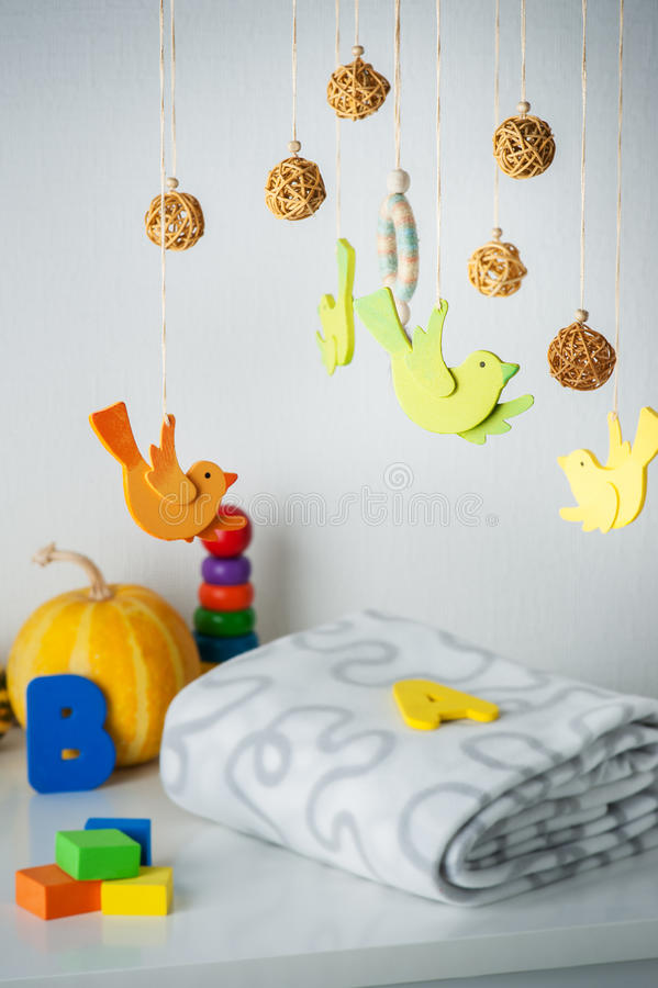 Baby crib mobile and kids toys. In white interior stock photo