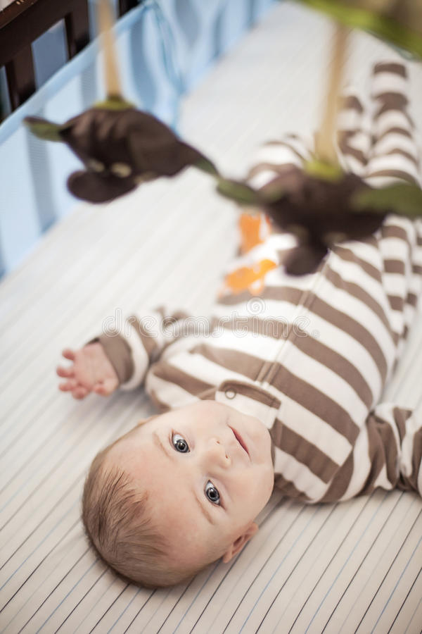 Baby in crib under mobile royalty free stock photo