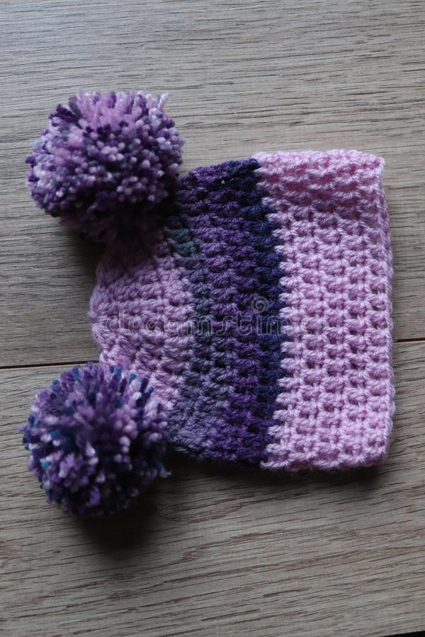 Baby crochet poncho and hat. Wooden yarn used to make baby clothing .poncho and hat in purple wooden yarn stock photos