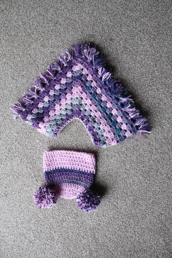 Baby crochet poncho and hat. Woollen yarn used to make baby clothing .poncho and hat in purple wooden yarn royalty free stock photos