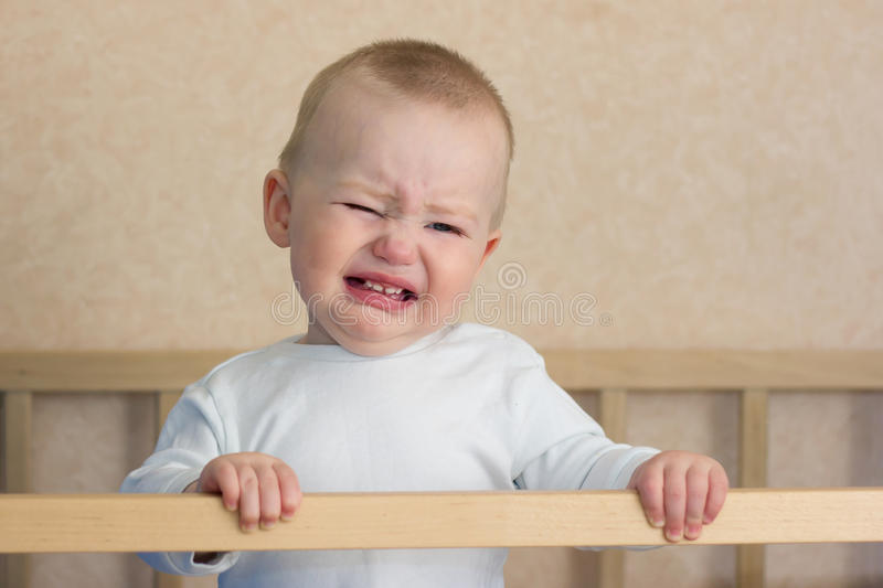 Baby cry in cot. Crying baby boy is standing in cot bed stock images