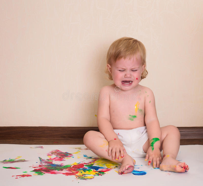 Baby crying. Dirty child drawing with her fingers. Toddler paint royalty free stock photography