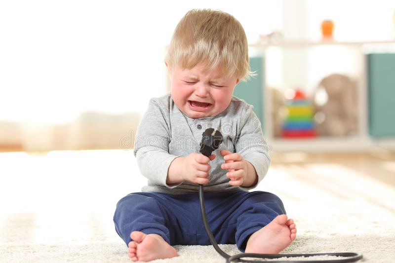 Baby crying holding an an electric plug royalty free stock photos