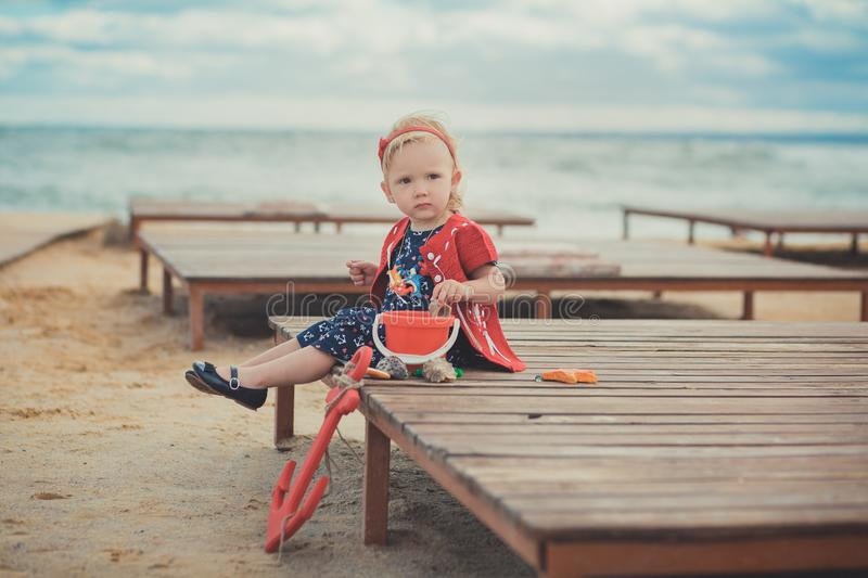 Baby cute girl with blond hair and pink apple cheek enjoying summer time holiday posing in beautiful beach full of sand wearing st. Ylish dress royalty free stock image