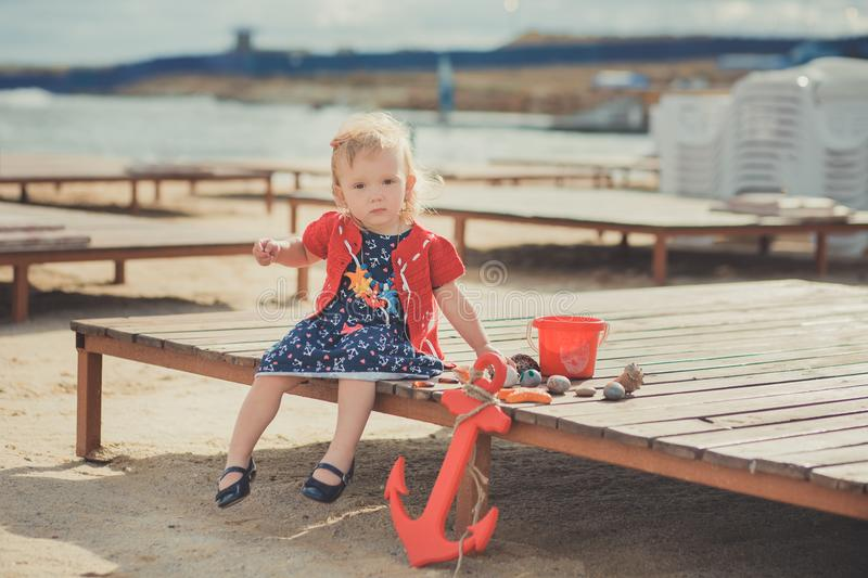 Baby cute girl with blond hair and pink apple cheek enjoying summer time holiday posing in beautiful beach full of sand wearing st. Ylish dress stock image