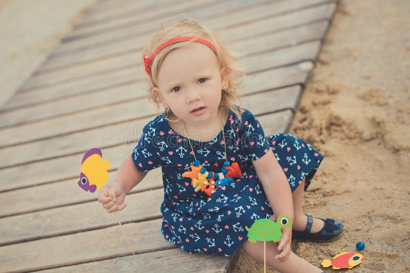 Baby cute girl with blond hair and pink apple cheek enjoying summer time holiday posing in beautiful beach full of sand wearing st. Ylish dress stock photography