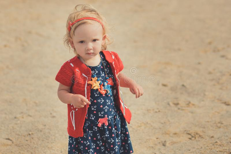Baby cute girl with blond hair and pink apple cheek enjoying summer time holiday posing in beautiful beach full of sand wearing st. Ylish dress stock photo