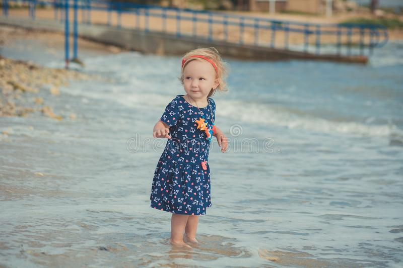 Baby cute girl with blond hair and pink apple cheek enjoying summer time holiday posing in beautiful beach full of sand wearing st. Ylish dress royalty free stock photography