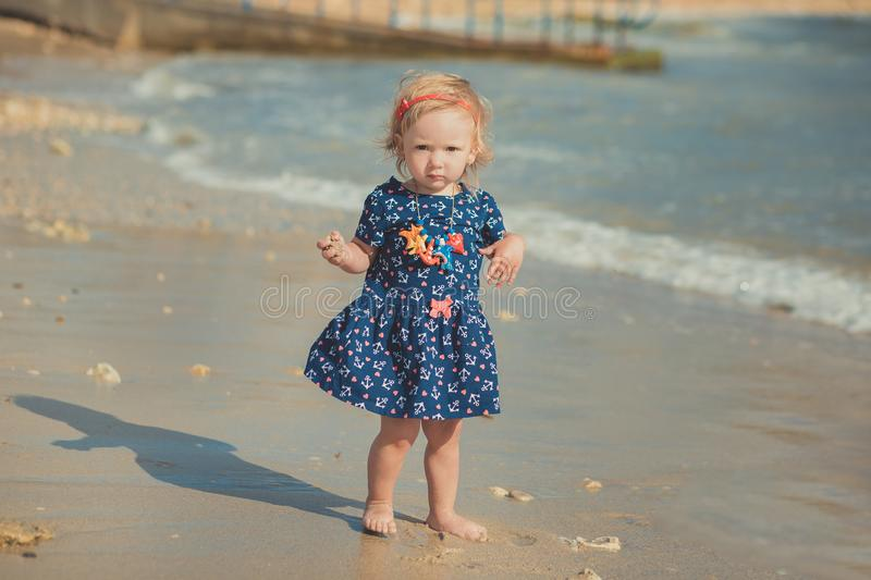 Baby cute girl with blond hair and pink apple cheek enjoying summer time holiday posing in beautiful beach full of sand wearing st. Ylish dress stock photos