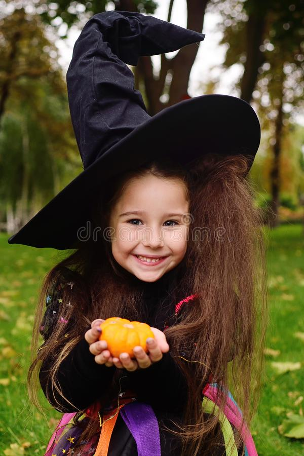 Girl in carnival costume and in hat of witch with little pumpkin in hands on halloween smiling at camera royalty free stock photography