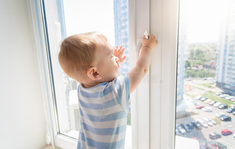 Baby in danger. Baby pulling handle of window royalty free stock image