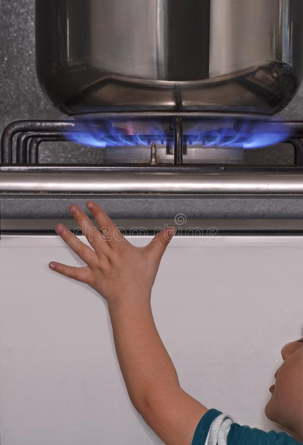 Baby danger gas stove. Child approach hand to a burner gas stove top in kitchen. Danger of child burner in the kitchen stock photography