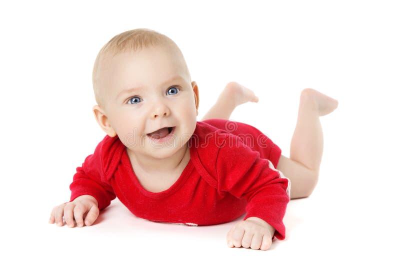 Baby, das über weißes, glückliches Kind in den Raupen sich hinlegen kriecht stockbild