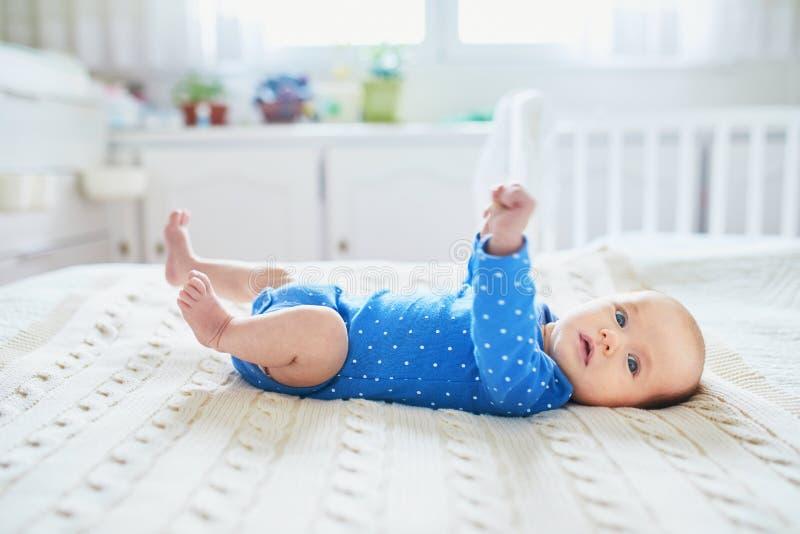 Baby, das auf Bett in der Kindertagesstätte liegt lizenzfreies stockbild