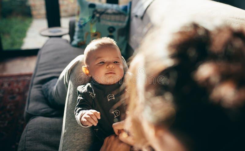 Baby, das auf den Beinen seiner Mutter schläft lizenzfreie stockbilder