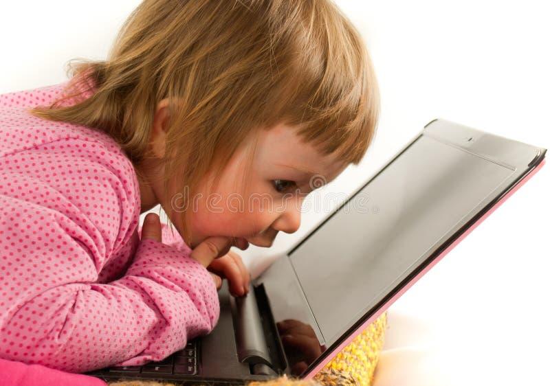 Baby, das auf den Bildschirm des Laptops schaut stockbilder
