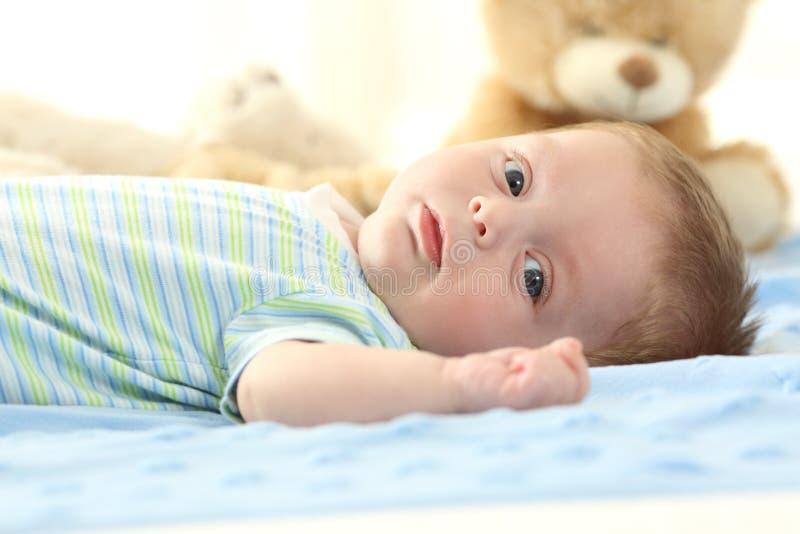 Baby, das auf einem Bett liegt und Sie betrachtet stockfotografie