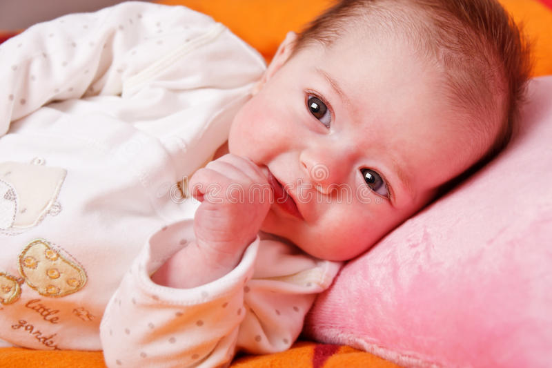 Baby, das auf einer weichen Decke und einem Überwachen liegt stockbilder