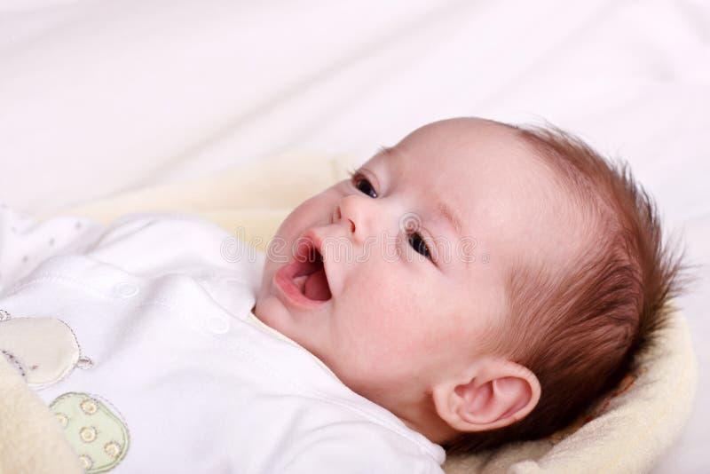 Baby, das auf einer weichen Decke und einem Überwachen liegt stockfotos