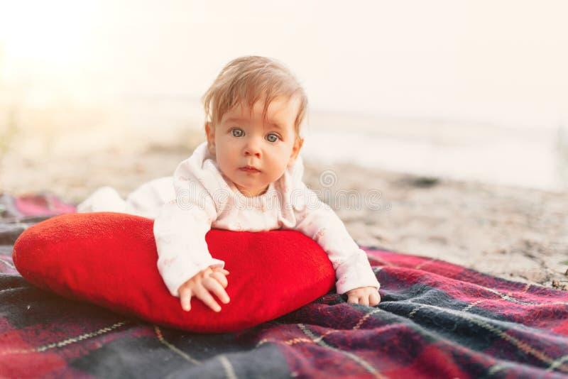 Baby, das auf rotem umfassendem im Freien liegt Selektiver Fokus auf ihren Augen lizenzfreie stockfotos
