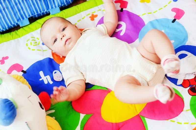 Baby, das auf sich entwickelnder Wolldecke liegt stockfotografie