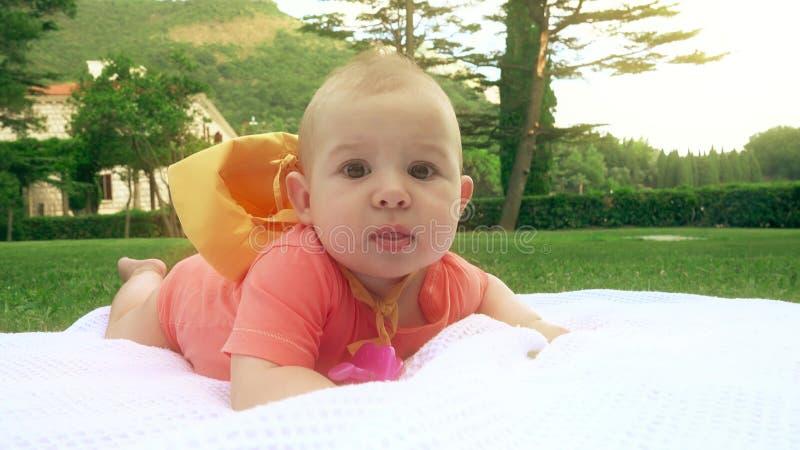 Baby, das auf das Tuch auf grünem Gras, Nahaufnahmeschuß legt stockbild