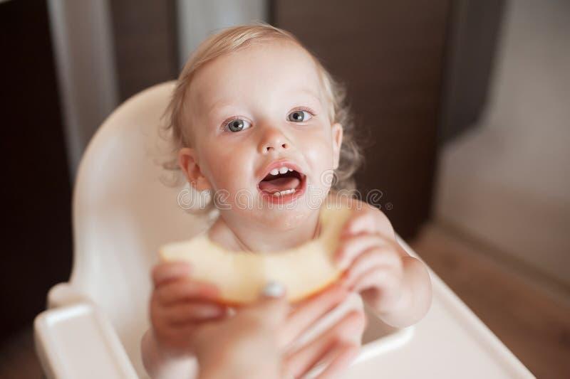 Baby, das Blatthonig-Melone isst Lustiges lachendes Kind in der Küche Nettes Kind im Hochstuhl lizenzfreies stockfoto