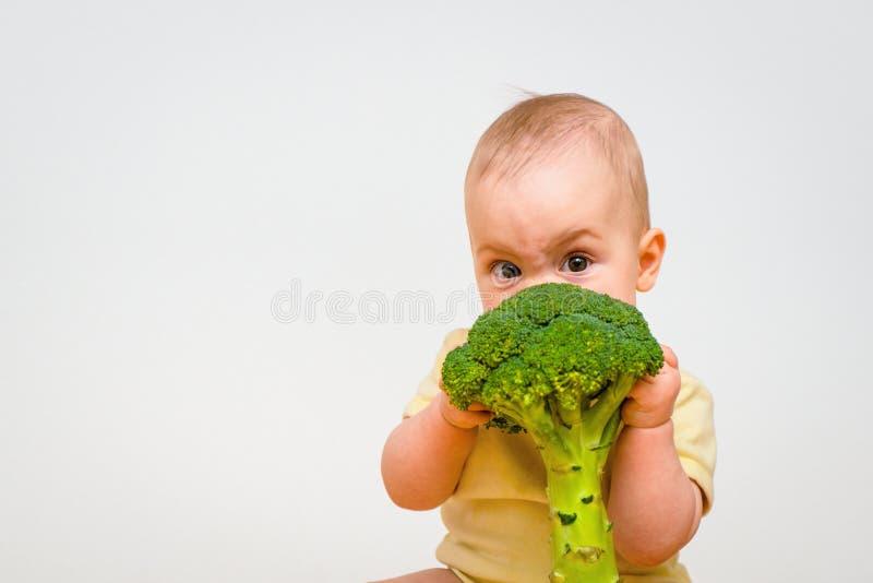 Baby, das Brokkoli isst lizenzfreies stockfoto
