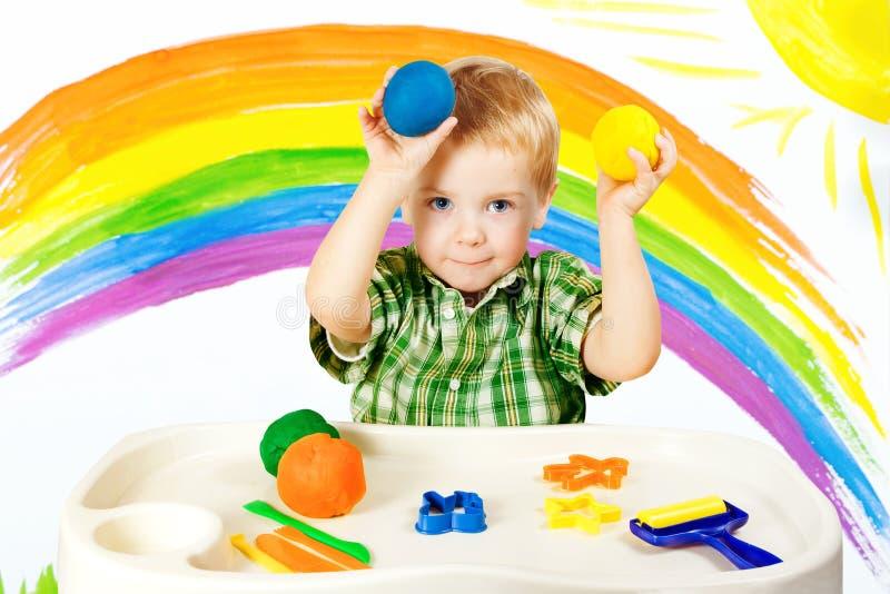 Baby, das bunten Lehm, Kinderfarbteig-Bälle, Kinderkunst modelliert lizenzfreies stockfoto