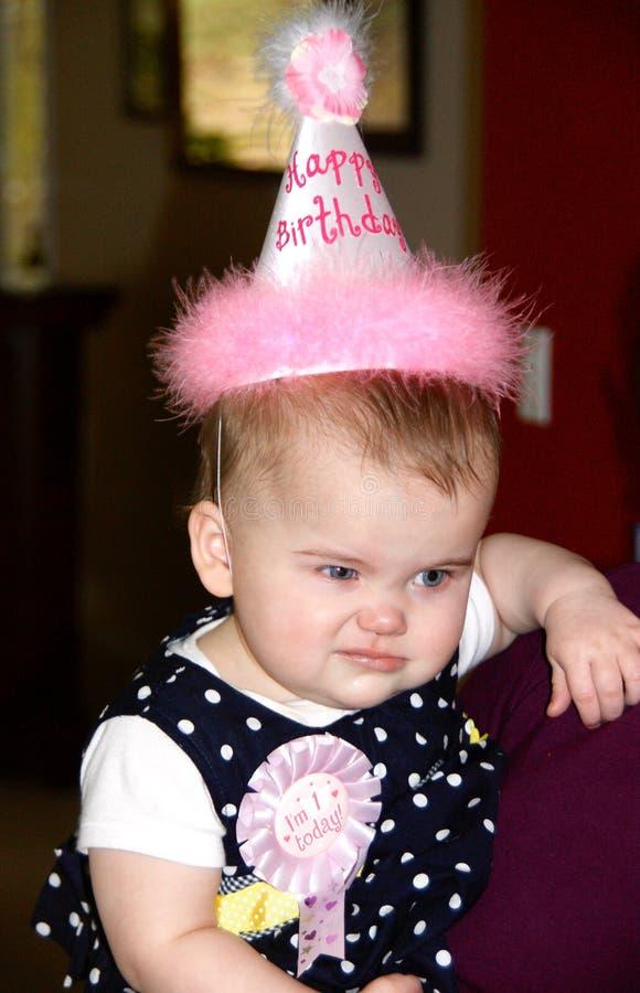 Baby, das ein lustiges Gesicht an ihrer ersten Geburtstagsfeier macht lizenzfreie stockbilder