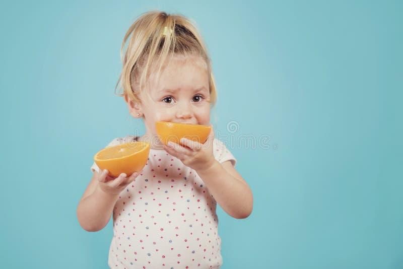 Baby, das eine Orange isst stockfotografie
