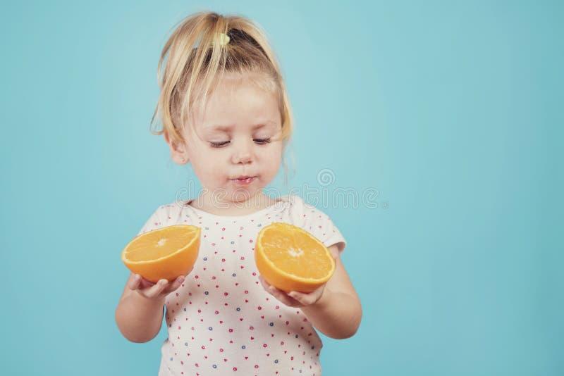 Baby, das eine Orange isst lizenzfreies stockfoto