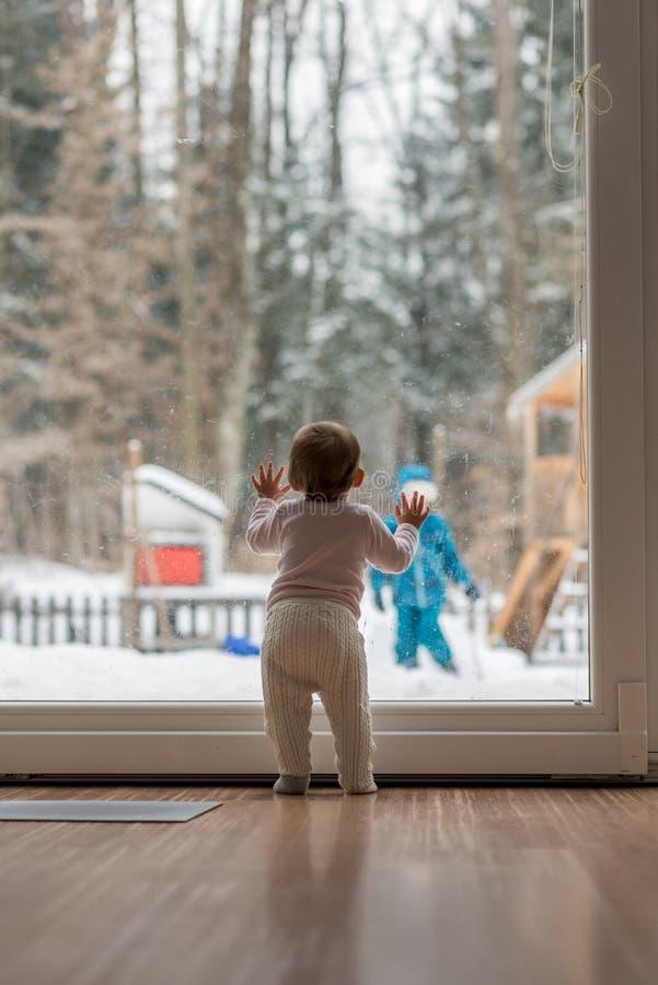 Baby, das an einem Fenster draußen aufpasst ihren Winkel des Leistungshebels des Bruders steht lizenzfreie stockfotografie
