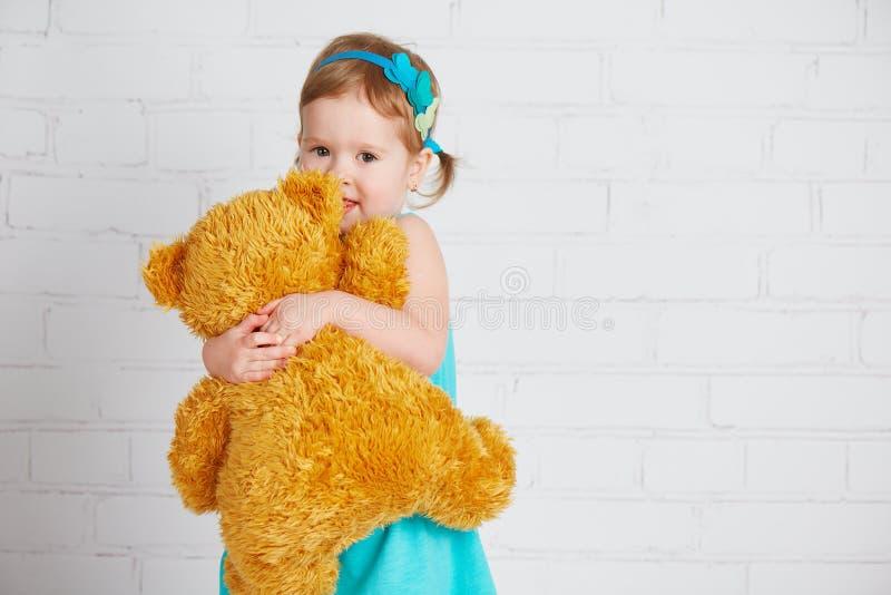 Baby, das einen geliebten Teddybären umarmt lizenzfreie stockbilder