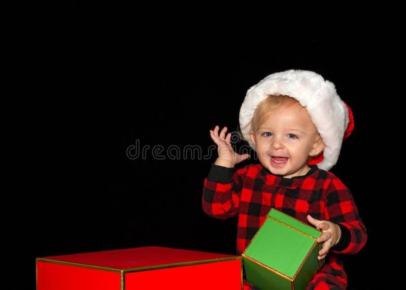 Baby, das einen Sankt-Hut lächelt trägt, Weihnachtsgeschenke halten lizenzfreie stockbilder