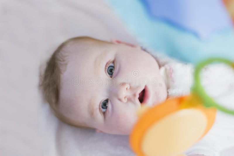 Baby, das entlang des mobilen Spielzeugs anstarrt stockbilder