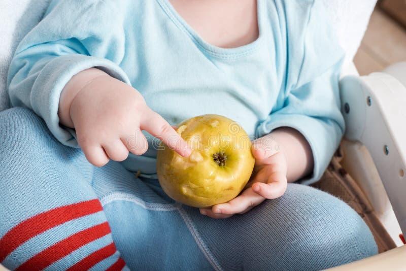 Baby, das Frucht isst Bei?ender Apfel des kleinen Jungen, der im wei?en Hochstuhl in der sonnigen K?che mit Fenster und Wanne sit lizenzfreies stockfoto