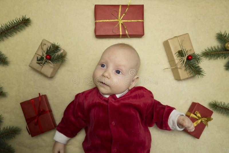 Baby, das glückliches umgeben durch Weihnachtsgeschenke glaubt stockfoto