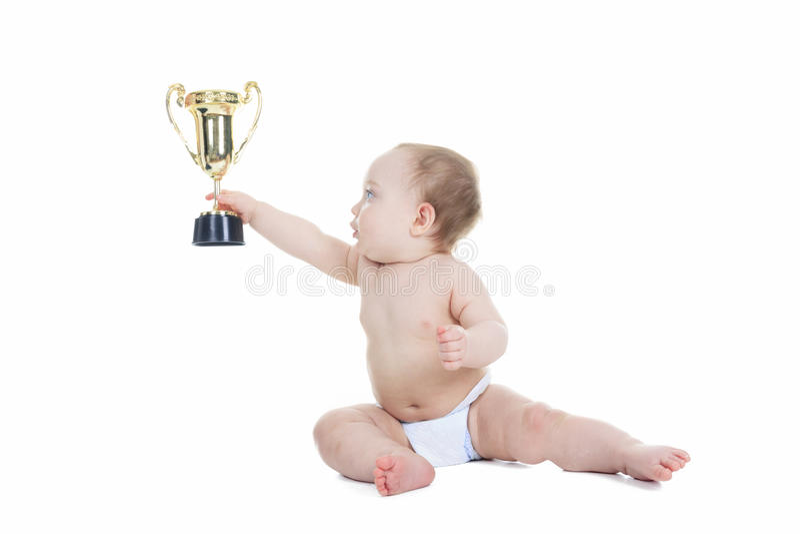 Baby, das Goldtrophäenschale auf einem weißen Hintergrund hält stockbild