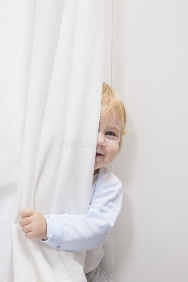 Baby, das hinter Vorhang späht lizenzfreie stockfotografie