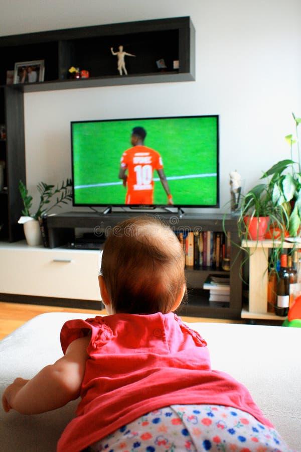 Baby, das im Fernsehen einen Fußball aufpasst lizenzfreies stockfoto