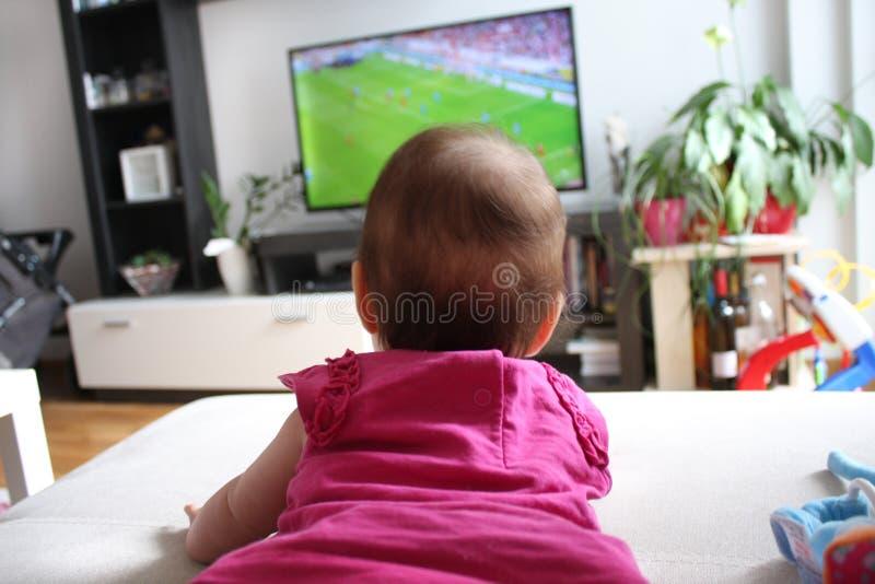 Baby, das im Fernsehen einen Fußball aufpasst lizenzfreies stockbild